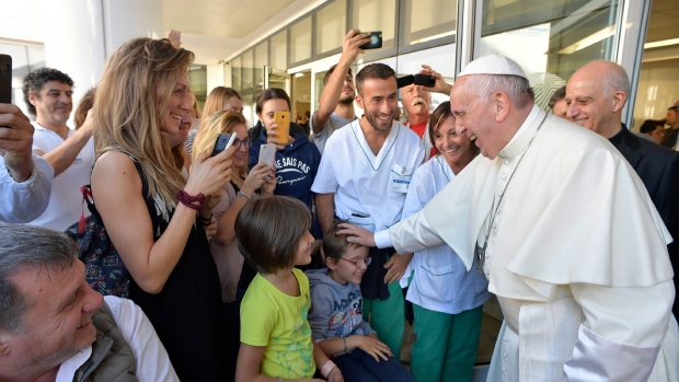 Pope Francis caresses a child during his visit to the Santa Lucia Foundation in Rome, Friday, Sept. 22, 2017. (L'Osservatore Romano/Pool Photo via AP)
