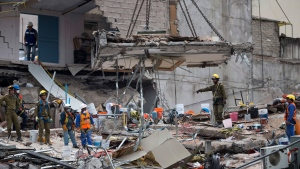 A crane removes a slab of concrete at the site of a felled office building brought down by a 7.1-magnitude earthquake, in the Roma Norte neighborhood, in Mexico City, Saturday, Sept. 23, 2017. As rescue operations stretched into Day 5, residents throughout the capital have held out hope that dozens still missing might be found alive. (AP Photo/Moises Castillo)