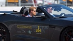 Prince Harry rides shotgun in a car with a member of team Germany at the Jaguar Land Rover Challenge at the Invictus Games in Toronto on Saturday, September 23, 2017. THE CANADIAN PRESS / Chris Donovan