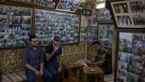 A Kurdish peshmerga soldiers sits inside a tea house in downtown Irbil where the walls are covered with photographs of historic Kurdish independence fighters, Saturday, Sept. 23, 2017. Iraq's Kurdish region will vote on Monday's referendum for Kurdish independence, a vote dismissed as illegal and destabilising by the central government and the international community. (AP Photo/Bram Janssen)