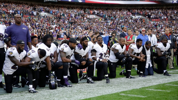Baltimore Ravens players, including former player Ray Lewis, second from right, kneel down during the playing of the U.S. national anthem before an NFL football game against the Jacksonville Jaguars at Wembley Stadium in London, Sunday Sept. 24, 2017. (AP / Matt Dunham)