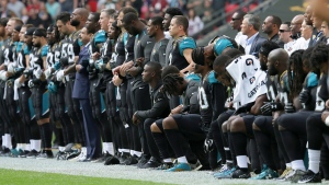 Jacksonville Jaguars players lock arms and kneel down during the playing of the U.S. national anthem before an NFL football game against the Baltimore Ravens at Wembley Stadium in London, Sunday Sept. 24, 2017. (AP / Tim Ireland)