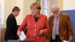 German Chancellor Angela Merkel holds her ballot as she walks to the election booth before casting her vote in Berlin, Germany, Sunday, Sept. 24, 2017. Merkel is widely expected to win a fourth term in office as Germans go to the polls to elect a new parliament. (AP Photo/Markus Schreiber)