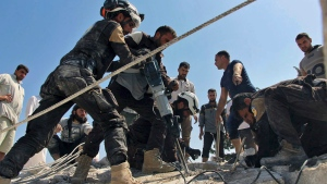 This photo provided by the Syrian Civil Defense White Helmets, which has been authenticated based on its contents and other AP reporting, shows Civil Defense workers using machinery to search through the rubble after airstrikes hit in Khan Sheikhoun, in the northern province of Idlib, Syria, Sunday, Sept, 24, 2017. (Syrian Civil Defense White Helmets via AP)