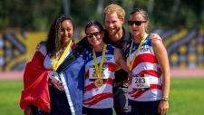 Prince Harry poses with women's 100-metre dash medallists (left to right) Sabrina Daulaus of France (silver), Sarah Rudder of the USA (gold) and Christy Wise of the USA (bronze) at the Invictus Games in Toronto on Sunday, Sept. 24, 2017. THE CANADIAN PRESS/Chris Donovan