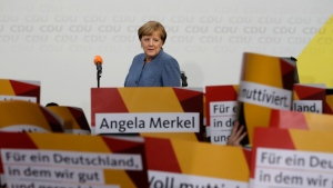 Supporters hold posters as German Chancellor Angela Merkel returns on the stage at the headquarters of the Christian Democratic Union CDU in Berlin, Germany, Sunday, Sept. 24, 2017 after the German parliament election. (AP Photo/Michael Sohn)