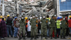 Rescue workers and volunteers stand in the middle of the street after an earthquake alarm sounded and a small tremor was felt during rescue operations at the site of a collapsed building in Roma Norte, in Mexico City on Saturday, Sept. 23, 2017. (AP / Rebecca Blackwell)