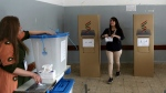 An Iraqi Kurdish woman leaves the voting booth to cast her ballot in the referendum on independence from Iraq in Irbil, Iraq on Monday, Sept. 25, 2017. (AP / Khalid Mohammed)