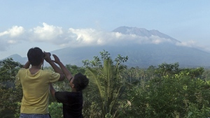 A man observes the Mount Agung with binoculars at a viewing point in Bali, Indonesia on Wednesday, Sept. 20, 2017. (AP / Firdia Lisnawati)