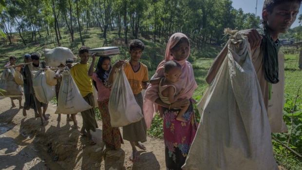 Newly arrived Rohingya Muslim family, who crossed over from Myanmar into Bangladesh, carry their belonging as they arrive at Kutupalong refugee camp, Bangladesh on Sunday, Sept. 24, 2017. (AP / Dar Yasin)