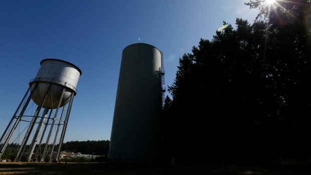 In this Sept. 15, 2017 photo, the current water tower used at the Special Commitment Center on McNeil Island, Wash., sits at right, next to an older and currently unused tower. Scores of sex offenders ordered to live on the secluded island say the water there is making them sick and causing unexplained deaths, and records show the water system has been plagued by problems for more than a decade. (AP Photo/Ted S. Warren)