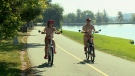 May McKinnis (left) rides her bike topless alongside her husband Walter McKinnis on a hot and humid day in Ottawa on September 25, 2017.