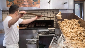 Fresh bagels are removed from the oven at the St-Viateur bagel shop, Sunday, May 21, 2017 in Montreal. (Paul Chiasson/The Canadian Press)