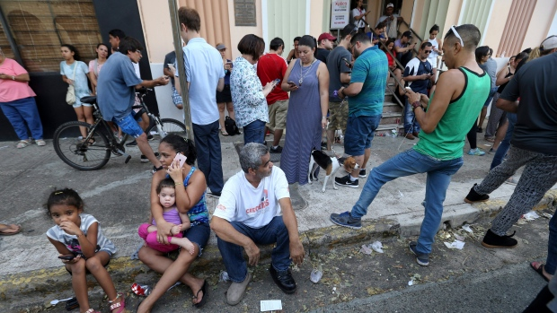 People use their devices to communicate at a working Wi-Fi hotspot in San Juan, Puerto Rico, on Sunday, Sept. 24, 2017. (AP Photo/Gerald Herbert)