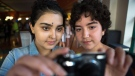 Cancer patients Yasmine Dabir, 17, left, and Salome Oliveira dos Santos take a picture with one of the cameras supplied by the hospital for the photo voice project, on display at the Sick Kids Hospital in Toronto on Monday, Sept. 25, 2017. THE CANADIAN PRESS/Chris Donovan