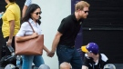 Prince Harry, right, arrives with his girlfriend M