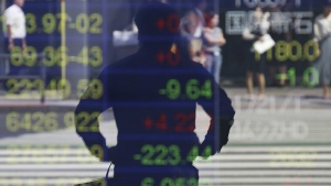A man is reflected on the electronic board of a securities firm in Tokyo, Monday, Sept. 25, 2017. (AP / Koji Sasahara)