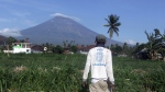 A villager watches Mount Agung volcano in his field in Amed, Bali, Indonesia on Tuesday, Sept. 26, 2017. (AP / Firdia Lisnawati)