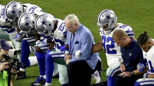 The Dallas Cowboys, led by owner Jerry Jones, centre, take a knee prior to the national anthem prior to an NFL football game against the Arizona Cardinals in Glendale, Ariz. on Monday, Sept. 25, 2017. (AP / Matt York)