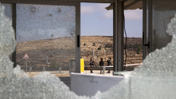 Israeli security officers are seen through bullets shattered windows of the check point at the entrance to Har Adar settlement near Jerusalem, on Sept. 26, 2017. (Ariel Schalit / AP)