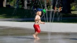 A child plays in a splash pad in Toronto during a September heat wave.