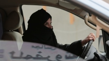 In this Saturday, March 29, 2014 file photo, Aziza Yousef drives a car on a highway in Riyadh, Saudi Arabia, as part of a campaign to defy Saudi Arabia's ban on women driving. (AP Photo/Hasan Jamali, File)
