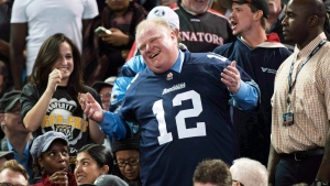 Former Toronto Mayor Rob Ford laughs with fans as he attends the Toronto Argonauts and Hamilton Tiger-Cats CFL Eastern Conference final football game in Toronto on Sunday, Nov. 17, 2013. (Nathan Denette/The Canadian Press)