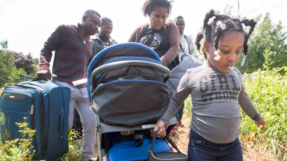 Asylum seekers cross the border in Hemmingford, Que., on Friday, August 4, 2017. (Ryan Remiorz/The Canadian Press)