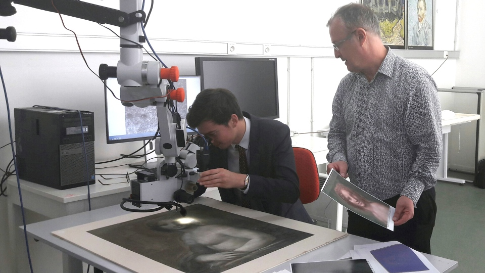 In this photo provided by the Conde museum, Chateau de Chantilly, and dated Wednesday, Sept. 27, 2017, chief curator of heritage, Bruno Mottin, left, examines a charcoal sketch through a microscope, depicting a nude woman while Mathieu Deldicque, curator at Conde museum, looks on, at the Center for Research and Restoration of the Museums of France in Paris, France. (Domaine de Chantilly via AP)