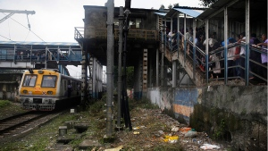 A local train drives past a pedestrian bridge where a stampede occurred earlier in the morning in Mumbai, India, Friday, Sept. 29, 2017. (AP / Rafiq Maqbool)