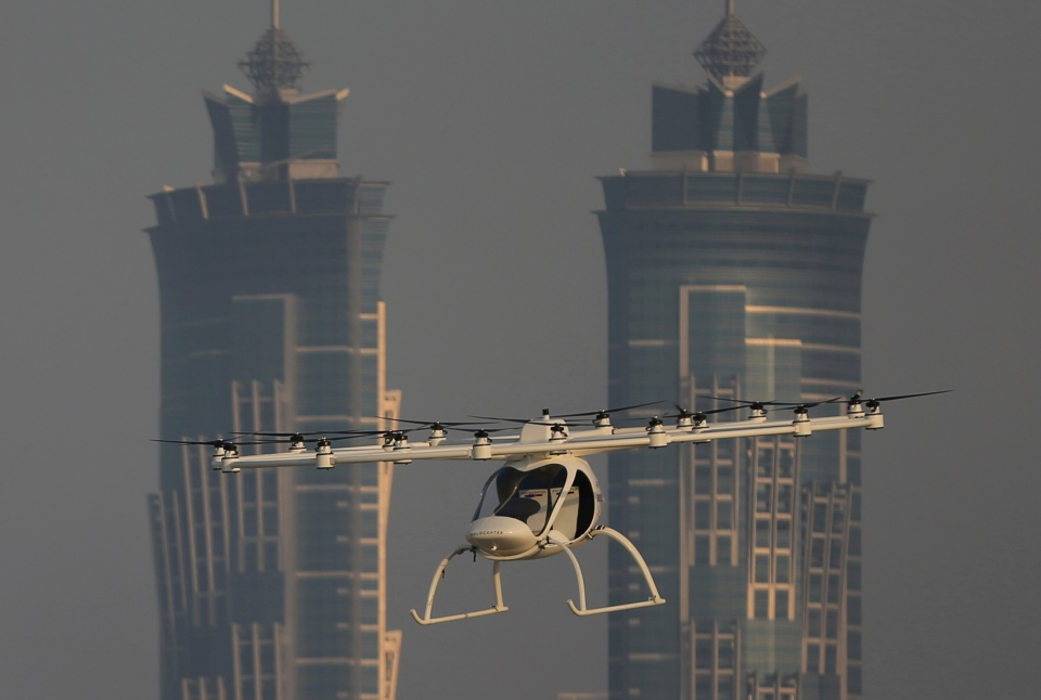 In this Sept. 26, 2017 photo, a Volocopter prototype flies in front of the two hotel towers during a test flight in Dubai, United Arab Emirates.(AP Photo/Kamran Jebreili)