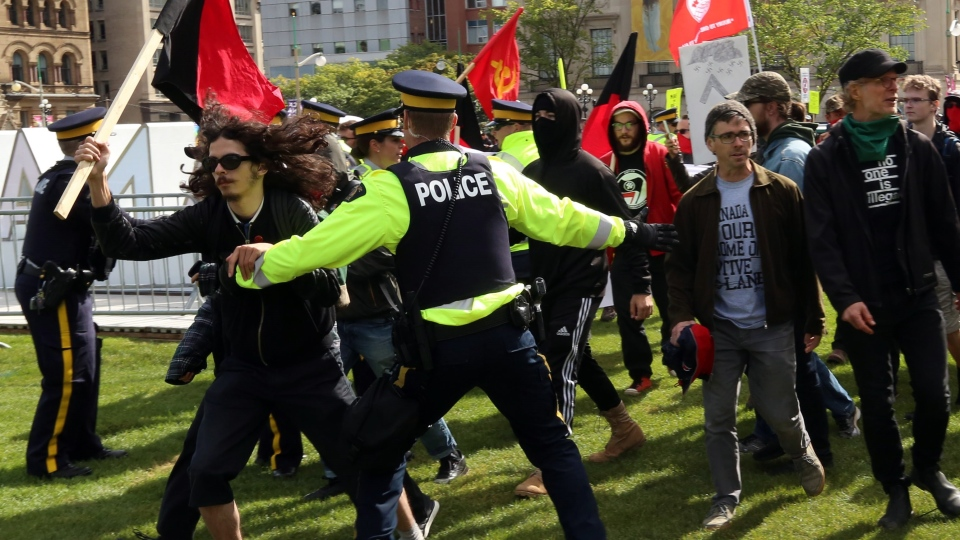Anti-fascist demonstrators rush through RCMP police lines in an attempt to get closer to a small group of anti-immigration demonstrators on Parliament Hill in Ottawa on Saturday, September 30, 2017. THE CANADIAN PRESS/Fred Chartrand