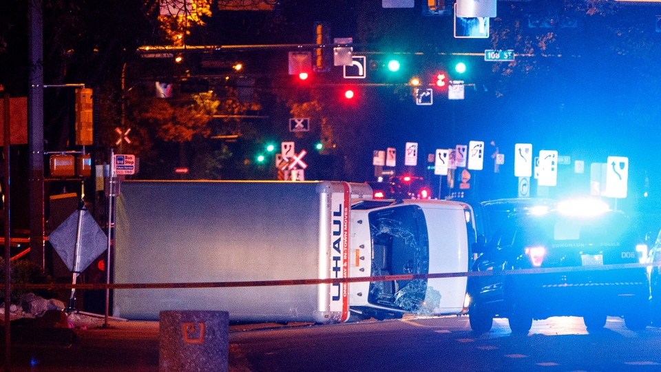 Police investigate the scene after a cube van ran into pedestrians and later flipped over while being pursued by police, in Edmonton on Saturday September 30, 2017. (THE CANADIAN PRESS/Jason Franson)