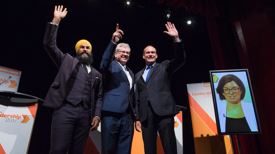 Jagmeet Singh, from left to right, Charlie Angus and Guy Caron pose for a photograph as Niki Ashton, is seen on a television screen via satellite from Ottawa, before the final federal NDP leadership debate in Vancouver on September 10, 2017. THE CANADIAN PRESS/Darryl Dyck
