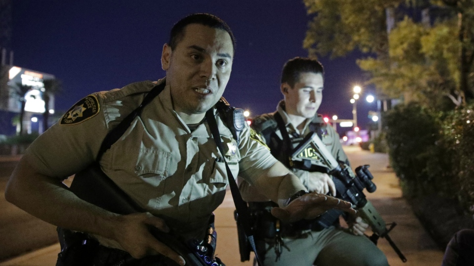 Police officers advise people to take cover near the scene of a shooting near the Mandalay Bay resort and casino on the Las Vegas Strip in Las Vegas on Sunday, Oct. 1, 2017. (AP / John Locher)