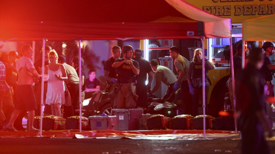 Medics treat the wounded as Las Vegas police respond during an active shooter situation on the Las Vegas Stirp in Las Vegas on Sunday, Oct. 1, 2017. (Chase Stevens / Las Vegas Review-Journal)