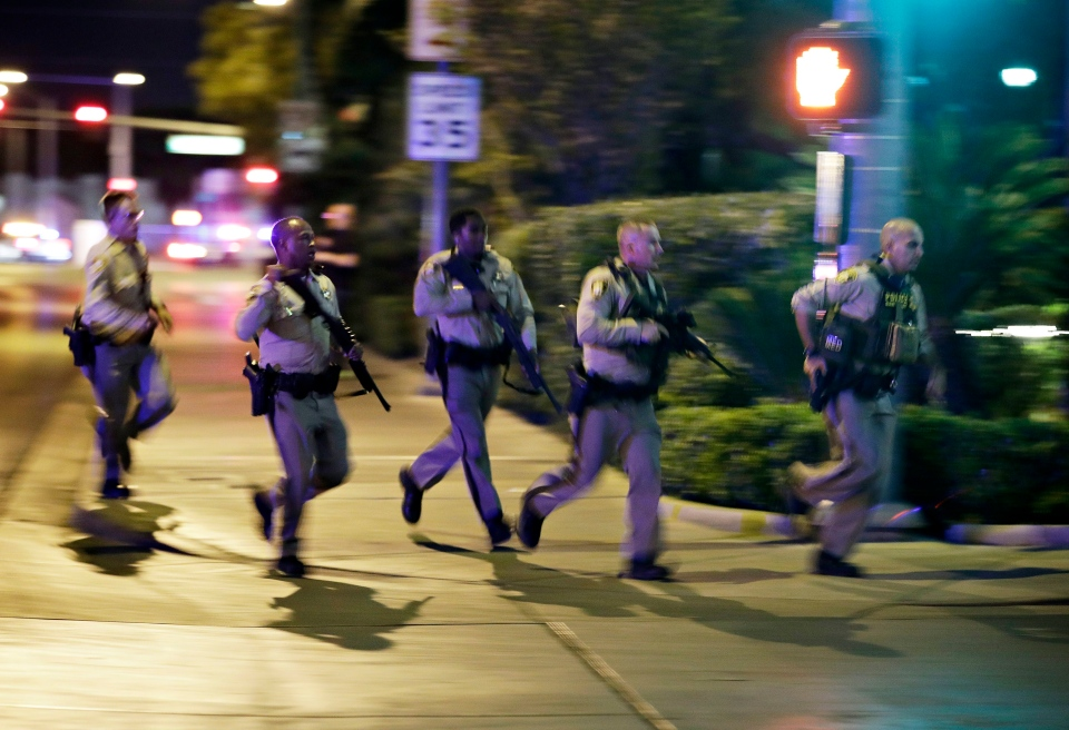 Police run to cover at the scene of a shooting near the Mandalay Bay resort and casino on the Las Vegas Strip, Sunday, Oct. 1, 2017, in Las Vegas. (AP Photo/John Locher)