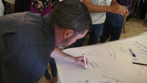 Bill Fortier signs a banner, also signed by others who participated in the same program.