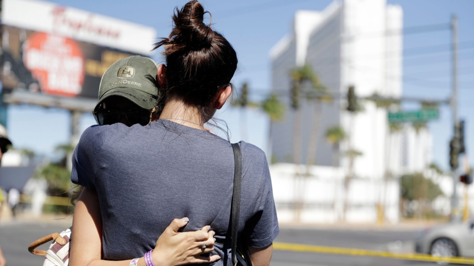 Aria James, with back to camera, and Jenna Kerr, from Ventura, Calif, embrace on the Las Vegas Strip near a concert venue where a mass shooting occurred in Las Vegas on Monday, Oct. 2, 2017. (Marcio Jose Sanchez/AP)