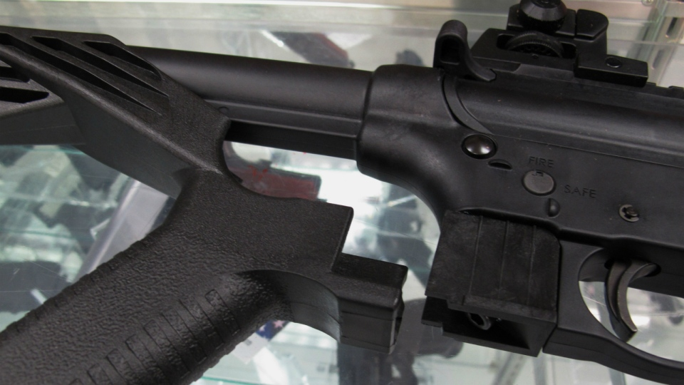 A 'bump' stock is seen next to a disassembled .22-caliber rifle at North Raleigh Guns in Raleigh, N.C. on Feb. 1, 2013. (AP / Allen Breed)