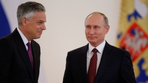 U.S. Ambassador Jon Huntsman, left, walks after presenting credentials to Russian President Vladimir Putin, right, during a ceremony in the Kremlin in Moscow, Russia, on Tuesday, Oct. 3, 2017. (AP / Pavel Golovkin)