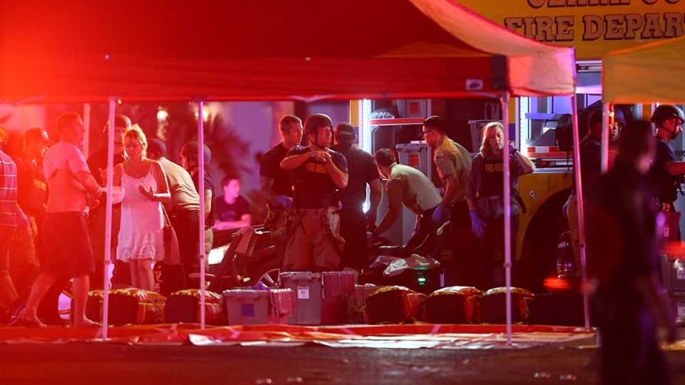 Medics treat the wounded as Las Vegas police respond during an active shooter situation on the Las Vegas Stirp in Las Vegas Sunday, Oct. 1, 2017. (Chase Stevens / Las Vegas Review-Journal via AP)