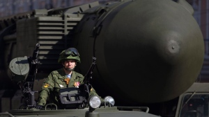 FILE -- An officer looks out of his armored vehicle with a Topol M intercontinental ballistic missile launcher seen at right before the parade rehearsal in Moscow, Russia, on Wednesday, May 7, 2014. (AP Photo/Ivan Sekretarev)