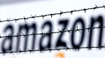 Amazon logo is seen behind barbed wire at the company's logistic centre in Rheinberg,Germany, on Feb. 19, 2013. (Frank Augstein / AP)