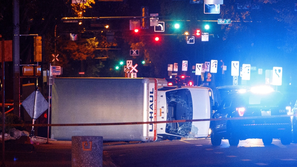 A U-Haul truck rests on its side after a high-speed chase with police in Edmonton Alta, on Sept. 30, 2017. (Jason Franson / The Canadian Press via AP)