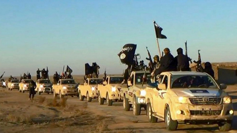 In this undated file photo released by a militant website, which has been verified and is consistent with other AP reporting, militants of the Islamic State group hold up their weapons and wave its flags on their vehicles in a convoy to Iraq, in Raqqa, Syria. (Militant website via AP, file)