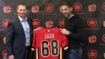 Flames Asst. GM Craig Conroy and Jaromir Jagr pose with a jersey following the official signing of the right winger