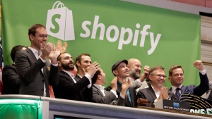 Shopify CEO Tobias Lutke, center wearing hat, is celebrated as he rings the New York Stock Exchange opening bell, marking the Canadian company's IPO, Thursday, May 21, 2015. (THE CANADIAN PRESS/AP-Richard Drew)