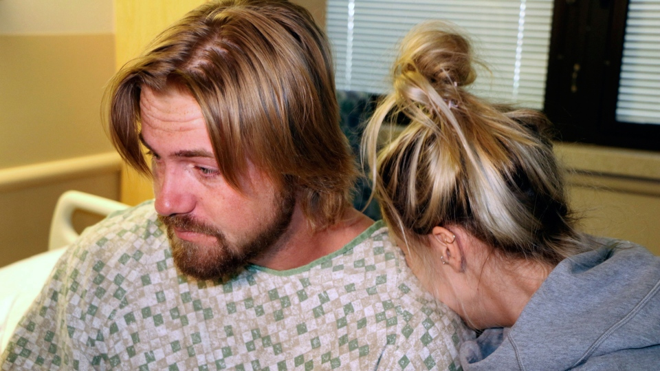 Amanda Homulos, right, hugs her boyfriend Braden Matejka at the Sunrise Hospital in Las Vegas, Wednesday, Oct. 4, 2017. The couple from Canada had traveled to Las Vegas to celebrate Matejka's 30th birthday. Matejka was shot in the back of the head by a gunman who opened fire on a music concert the couple were attending on Sunday. (AP Photo/Robert Ray)