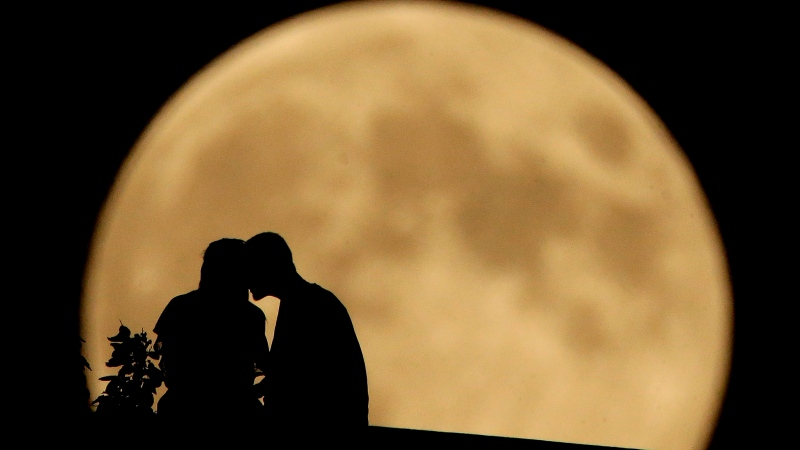A couple sits on a bluff overlooking the Missouri River as the harvest moon rises in the distance Monday, Sept. 8, 2014, in Kansas City, Mo. (AP Photo/Charlie Riedel)